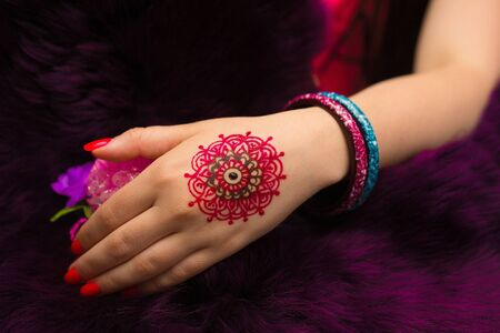 nails art: Indian picture on hands palm, mehendi tradition decoration, resistant design by special paint, brown, red, pink henna round mandala. Long nails new shape manicure. Saloon service art style, jewelry