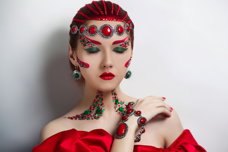 eyelids: Young beautiful girl, model, woman, Empress, Queen, character, ball, fairytale.Medieval, creative, theatrical style. Art bright makeup, red cheeks, lips, eyebrows, green eyes, patterns, eyelids, neck.