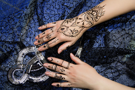 resistant: Picture on hands palms, mehendi tradition decoration, resistant design by special paint, brown, black henna tattoo. Long beige nails new shape manicure nail extension. Saloon service style, jewelry
