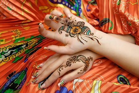 resistant: Indian picture on hands palms, mehendi tradition decoration, resistant design by special paint, brown, orange green henna. Long colorful nails new shape manicure nail extension. Saloon service style
