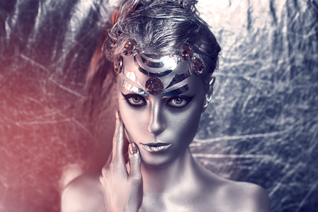 Portrait of beautiful young girl, woman, lady, hitman, killer, techno, future, progress. Ideal creative expressive makeup, silver skin, face, neck, shoulders, hand, arms. Stylish, bright, showy look.