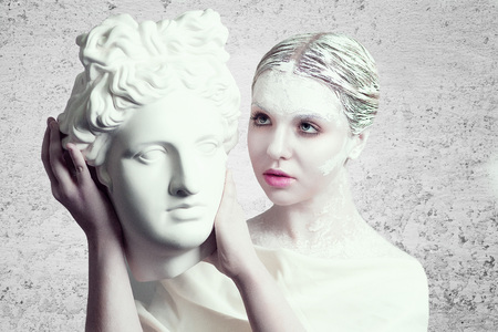 byzantium: White pretty girl holding a porcelain marble head of a statue ancient warrior. Make up idea, body art. Lower Empire, Byzantium style. Shoulders are decorated with draped garments. Woman, lady, female Stock Photo