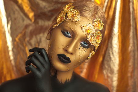 bodypaint: Magic golden girl with bright makeup. Streams of gold, shiny tears drops on the cheeks, black hand in the paint for body art. Big lips, long fingers, decorations, accesries. Professional photo, idea Stock Photo