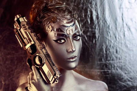 showy: Portrait of beautiful young girl, woman, lady, hitman, killer, techno, future, progress. Ideal creative expressive makeup, silver skin, face, neck, shoulders, hand, arms. Stylish, bright, showy look.