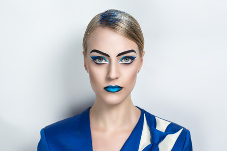 ultramarine blue: Beautiful young girl, lady, actress, model, character. Bold creative look, fashion style. Ideal expressive makeup, bright blue black lips, eye brows, arrows, design art ultramarine white business suit Stock Photo