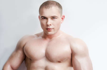 flawless: Perfect body of young handsome man. Athletic powerful person, cool boy, sweaty wet skin glossy effect, prepares flawless body for competition, muscles. Power lifting heavy weight, frees space for text Stock Photo