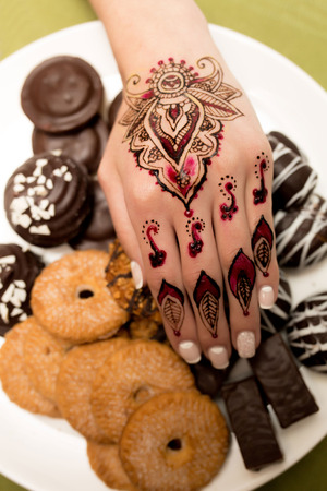 lacquer: Women beautiful hand with delicate fingers and a neat white lacquer manicures, henna art with decorative elements. Indian oriental style, ornamental patterns. Keep cookies, treats, sweets, tasty food Stock Photo
