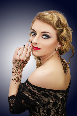 body painting: Young beautiful girl,model, woman, actress. Classy look, henna body painting, mehndi, hand, back. Expressive, spectacular, evening makeup, perfect skin, blue eyes, gray shadows, smoky eyes, red lips. Stock Photo