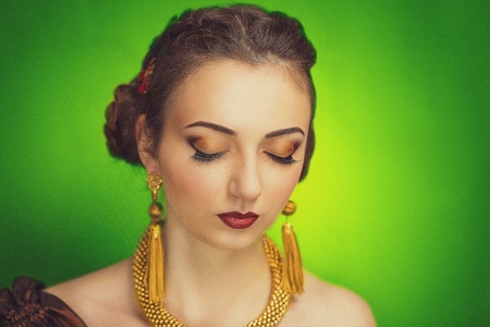 necked woman: Stylish woman with brown hairstyle brunette weaving, vinous lipstick, golden smoky eyes, gold luxury jewelry long ear rings, necklace, accessory, necked body, golden skin, Renaissance, Romanticism art Stock Photo