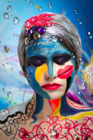 hallucinations: Surrealistic painting on the face of a beautiful young girl. The world of fantasy, illusions, hallucinations. The artist created a new underwater world, conceptual art, professional photo. Blue water