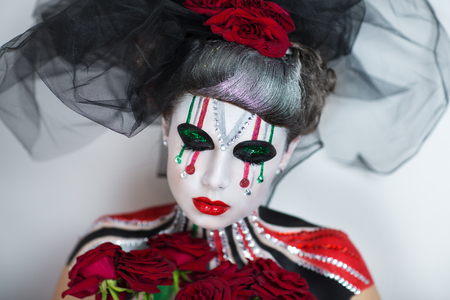 body painting: Young girl with creative body painting holding bouquet of red roses. Black Veil, silver hair design. The woman is a carnival character with colorful shiny stripes on face and shoulders. Halloween art