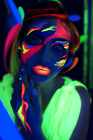 cosmo: Womans face with fluorescent make up art. Blue background. Studio shot. Pink, green, yellow neon paints. Creative idea good for clubs, disco, go-go, show concerts, parties. Sexy girl dark alien cosmo