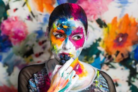 expressionism: Portrait of beautiful young girl, woman, lady,model,painting, canvas,art, painting,expressionism. Bright creative makeup, expressive eyes, paint, colorful, yellow, blue pink, white flowers. hand berry