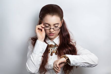 timekeeping: Studio shot of beautiful businesswoman, looking over her glasses on a wristwatch. Serious woman in white official blouse with watch on her hand, brown necklace. Hair dress curly brunette. Professional