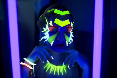 gogo girl: Gesicht der Frau mit fluoreszierenden bilden Kunst. Blauer Hintergrund. Studio gedreht. Orange, grün, gelb Neon Farben. Kreative Idee ist gut für die Clubs, Disco, Go-Go, Show Konzerte, Partys. Sexy girl alien cosmo