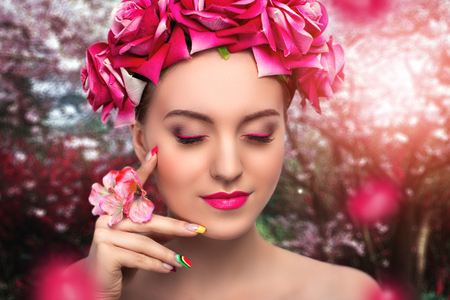 french manicure sexy woman: Young beautiful woman, lady, model, actress, fairy flowers.Desire, dream. Background, nature, blooming garden, sakura. Bright, expressive makeup, pink arrows, lipstick. Stylish hair accessories, roses