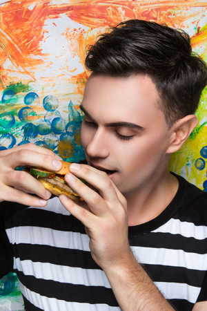 Stylish man close up portrait. Fashion hairstyle sexy bad boy. Black guy with fashionable haircut. banner conceptual idea about unhealthy food eating big meat hamburger, new effects success life style