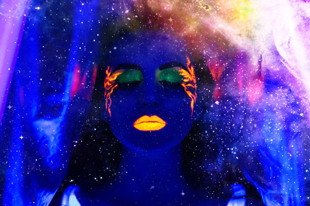 Creative colorful makeup neon, glowing painting on face ultraviolet picture, shiny orange fire on blue body. Sexy girl portrait, cosmos club go go dancing, star universe, beauty fashion conceptual art