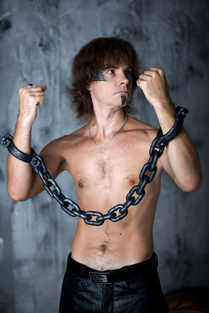 Young handsome man, boy, model, actor, hostage, slave, captive. Art makeup, paint, black, gray, temple, chin, long hair. Hands chained, desire,call to action, break, free themselves for pain, illness. Stock Photo