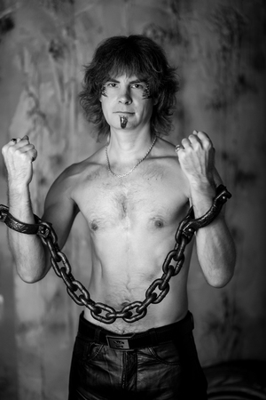 black and white photo of a man in shackles, handcuffs shackled his hands. Hostage in prison