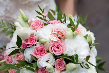 Big Bouquet and Two Wedding Rings. Goods for wedding. This photo is perfect for magazines, shops dealing with wedding dresses ceremonies bride groom marriage jewelry. Can be used for poster or website