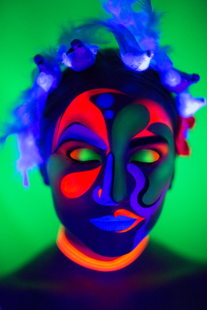 Creative woman lady girl model shine with blue orange colors. Bright concept conceptual art make-up glows under ultraviolet light. Club disco neon party time. Drink alcohol feel wild energy of music