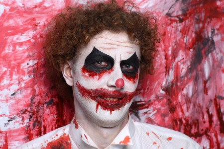 Creative make-up, conceptual crazy idea for Halloween night party. Eerie nightmare turning into zombie clown, volume spikes body art painting. Professional closeup photo. Bold skin injured, curly hair