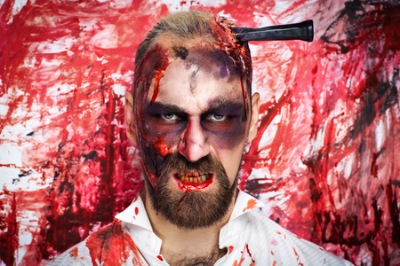 Creative man guy with a beard model blood red color wall. Bright conceptual art make-up glows light Halloween party time. Dark lifestyle, bad thoughts to eat person meat, destroy have funny weekend Stock Photo