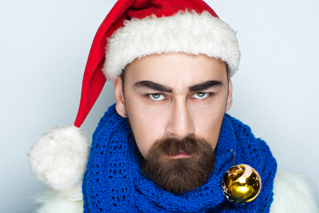 Handsome man Santa Claus looking into the camera, traditional red and white hat, blue knitted scarf, golden ball. Creative idea for Christmas party, horizontal photo with gray background good banner Stock Photo