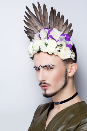 Boy man professional photo model Male gay, trendy Pharaoh in flower wreath, white purple roses. Closeup face art, small black choker, vertical professional photo. Perfect makeup, free place background Stock Photo
