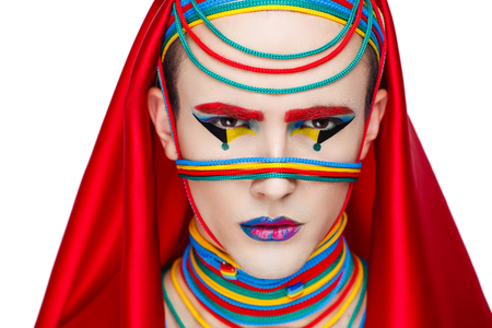 Boy man professional photo model Male gay, trendy Pharaoh in a red hood, rewound thread rope laces. Close up face art professional photo. Blue yellow green. Perfect make up, white clipped background