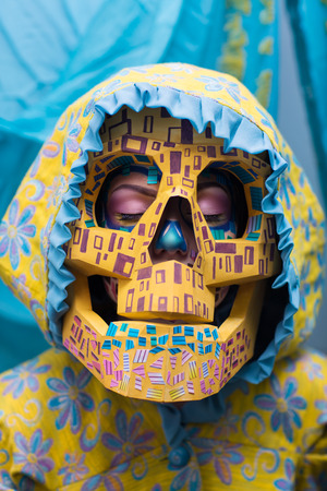 Woman with big face skull mask made of yellow paper. Creative make-up new conceptual idea for Halloween. blue yellow bold body art painting, flowers. Crazy graphic abstract picture lines surrealistic Stock Photo