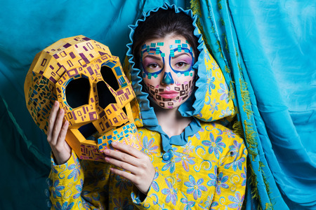 Woman with big face skull mask made of yellow paper. Creative make-up new conceptual idea for Halloween. blue yellow bold body art painting, flowers. Crazy graphic abstract picture lines surrealistic 스톡 콘텐츠