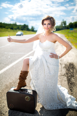 Beautiful blonde bride near the road is ready for new bright life Sunny day Outdoor  Long wedding dress, white veil, brown cow boy shoes like western film. She is thinking, waiting for prince husband Stock Photo