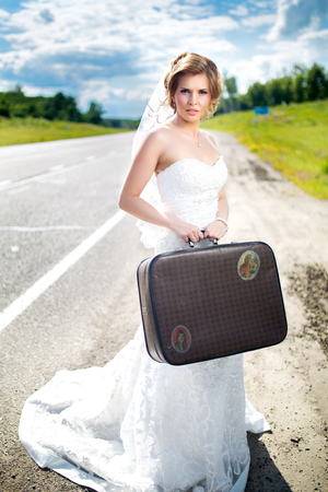 Beautiful blonde bride near the road is ready for a new bright life, sunny day, outdoor. Holding suitcase in her hand. Long wedding dress, white veil. turn around, look back. Pretty young woman love