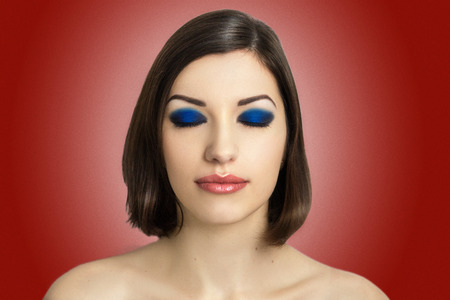 Healthy young girl, woman brunette with bright blue make up smoky eyes, pink (red, orange) lips, shape eyebrows, short hair style (hair dress), necked shoulders, perfect skin, studio, red background.