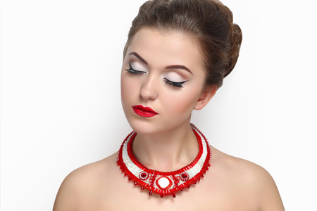 Portrait close-up of very beautiful perfect woman with bright make up, red velvet lipstick, necked shoulders, pretty face stylish hair do, necklace. Clean white wall photo studio background isolated.