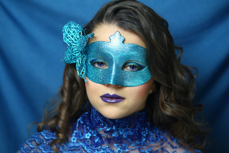 Beautiful girl in a blue carnival mask, close-up portrait. Actress in the theater, puppet, doll from the fairy tale about Pinocchio and Malvina. ultramarine lace dress collar. dark long curly hair do
