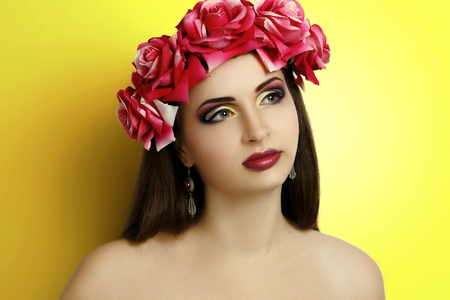Beautiful woman with professional make up, wreath of flowers, necked shoulders, near yellow studio wall. Closed eyes, dreams. Present for beautiful woman, spring bouquet of flowers. Portrait close-up Stock Photo