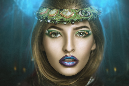 Magic woman with green jewelry on her head, purple lips, bright makeup. She looks like fortune teller or forest nymph, pretty fantastic creature from the fairy tail. Sexy big mouth, golden skin, hair Stock Photo