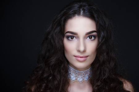 Beautiful girl woman lady with volume hair styling. Luxury brunette curly hairdo coiffure. Bright dark makeup, new tender beige lip-gloss lipstick. Professional photo model vip person closeup portrait Stock Photo