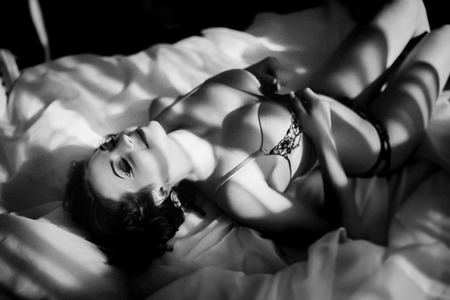 Sexy woman with perfect body, beautiful face. Girl lying on her back on a bed erotically arched back. Waiting for the return of men from work. Excitement, Passion. New Black and white horizontal photo