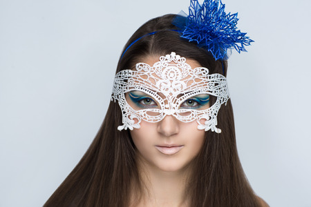 Young beautiful bright showy girl lady model snow queen. Fairy tale future party disco club. Art makeup flawless face blue flower accessory, hairdo eyebrows bright eyes nude beige lips. Facial mask