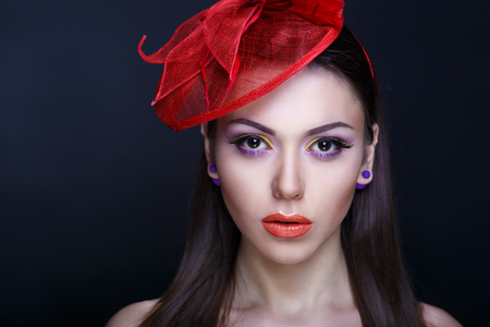 Closeup portrait of beautiful girl woman lady with volume combed hair styling. Luxury black brunette combed hair Bright makeup shiny lipstick cosmetics. Professional photo model vip person, red flower