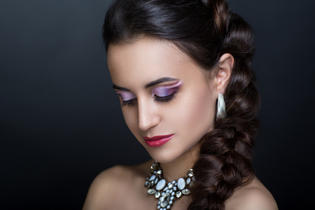 Young beautiful girl with a fashionable hairdo and professional makeup. Purple white eye shadows, perfect shape of brows, tender shiny pink lips color lipstick. Luxury accessory necklace with diamonds Stock Photo