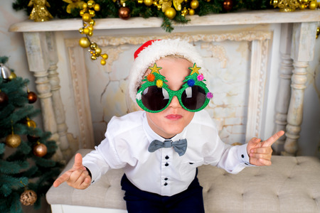 Creative funny boy seating on white chair at Christmas time. With colorful lights from Christmas tree, fireplace on background, selective focus. Horizontal banner, conceptual idea for New Year party