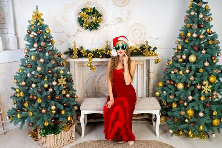 Beautiful woman in evening dress, young lady female near big x-mas fir-tree trees, happy New Year party golden decorations, accessory. Sexy santa girl sun-glass, dreaming about presents and surprises