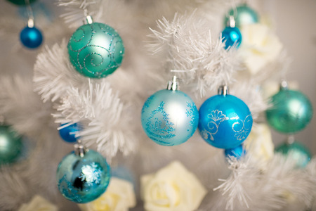 Beautiful decorations around x-mas trees fir-tree, happy New Year party. Santa Claus is coming, kids dreaming about presents, surprises. Shiny toys balls roses flowers bumps, blue white silver colors