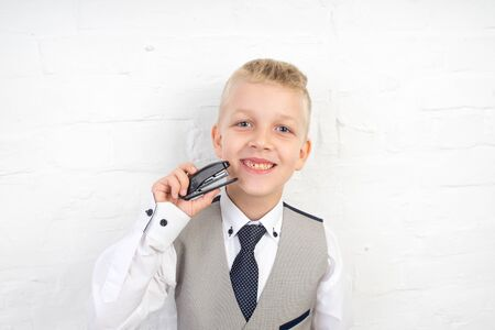 handsome blonde boy holding small stapler with staples in his hand. white wall studio, horizontal banner, professional photo. prepare for school, necessary office supplies. formal style business suit Stock Photo