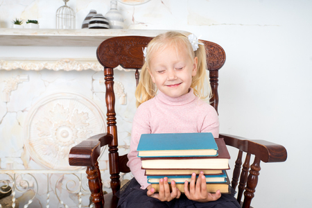 diligente: small beautiful girl holding in her hands stack of books educational literature. conceptual idea about modern education system. dreams about future profession, good diligent student in school, college